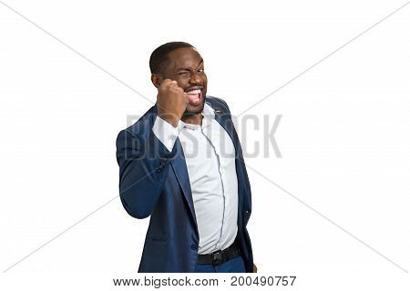Succesful businessman with raised fist. Cheerful black man in formal wear raised his fist as champion, side photo.