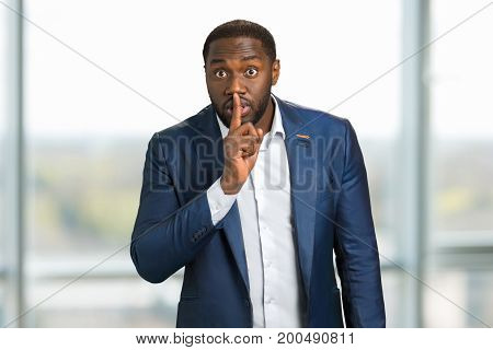 Businessman holding index finger on lips. Black man showing silence gesture with finger on his lips. Sign keep a silence.
