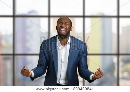 Crazy desperate black businessman crying. Shouting and crying man in formal wear in full desperate with raised fists.
