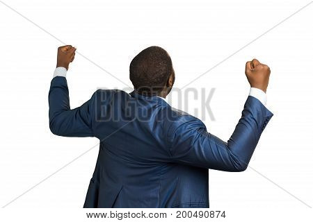 Back view of excited black businessman. Afro american manager raising hands, isolated on white background. Sign of victory and freedom.