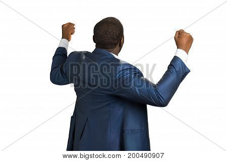 Rear view of successful businessman. Black manager standing with fists up. Man back celebrating. Back view portrait of businessman.