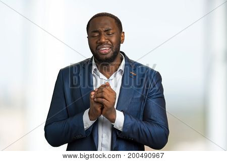 Worried businessman with closed eyes. Dark skinned manager with clasped hands praying and crying. Serious troubles of young executive and deep depression.