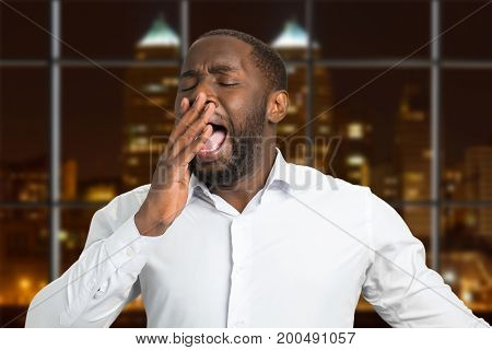 Yawn businessman on evening city background. Closeup portrait of yawning afro american manager in white shirt. Concept of overworking.
