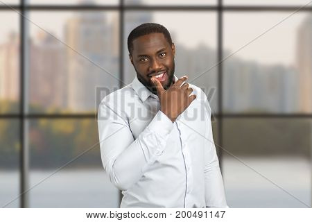Man in shirt holding thumb on lip. Smiling businessman put his thumb on lower lip, looking straight.