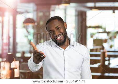 Black man in shirt pointing hand straight. Portrait of handsome man gesticulating with hand on blurred background.