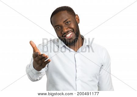 Dark skinned man with a hand outstretched. Smiling bearded man pointing at somebody with outstretched hand.