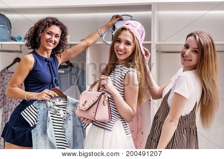 Happy funny female friends picking new clothes and accessories looking at camera in boutique.