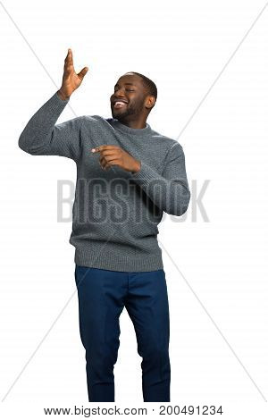 Happy black man showing direction. Man with raised right arm smile on white background.