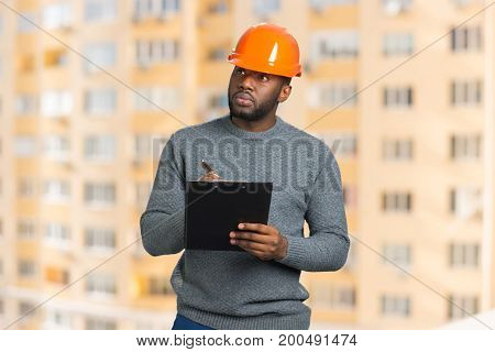 Construction supervisor writes on clipboard. Handsome engineer with black clipboard on blurred background.