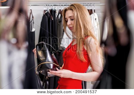 Caucasian young female shopper choosing leather backpack from new women s collection.