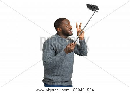 Cheerful black man taking selfie. Studio shot of young happy black afro american man smiling and raising fingers up while taking selfie. Positive guy smiling with monopod on white background.