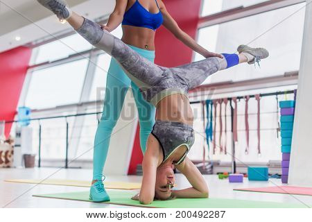 Fit young woman performing yoga headstand leg split with the help of a personal trainer in sports club
