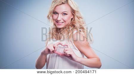 Smiling girl in white shirt showing heart with hands.