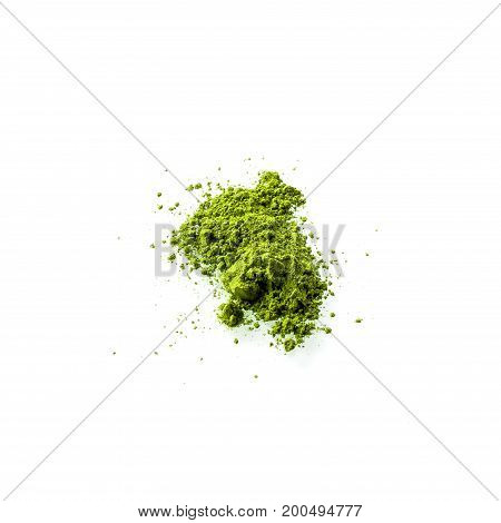 Matcha powder on white background flat view. Matcha is made of finely ground green tea powder. It's very common in japanese culture. Matcha is healthy due to it's high antioxydant count.