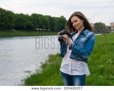 Beautiful girl tourist in a cotton jacket taking photos with a professional camera on the banks of the river in windy weather.