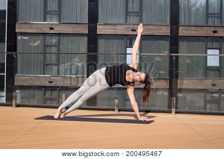 Young woman is doing Yoga fitness exercise outdoor on balcony with sea background