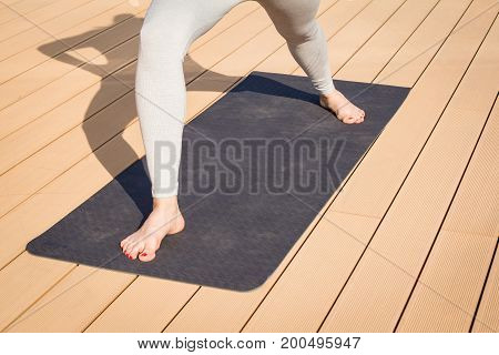close up picture of yoga mat on wooden table and legs of woman in asana