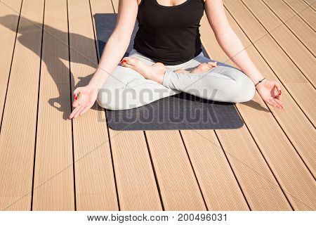Young lady practicing yoga on the balcony sea background, woman in lotus asans