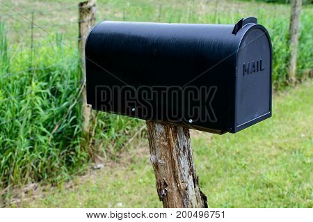 Black mail box on vintage wooden post outdoors near field in rural area. Conceptual sending mail and ordering online business background.