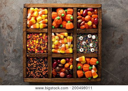 Halloween candy and sprinkles in wooden box overhead shot
