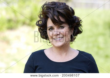 Attractive Middle aged woman with curly hair smiling in an outdoor setting