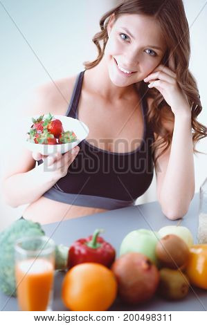 Girl sitting in the kitchen with fruit and glass of juice