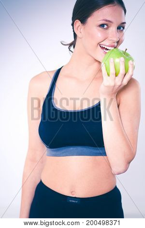 Happy young woman eating green apple isolated on white background.