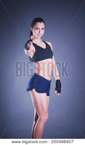 Portrait of a happy fitness woman showing ok sign