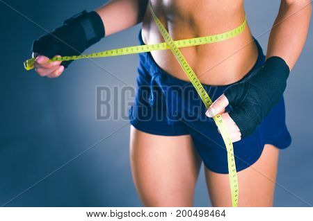 Fitness womans beautiful body with measure tape.