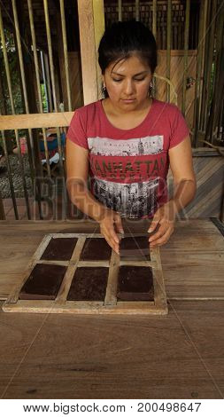 Puerto Quito, Pichincha / Ecuador - August 17 2017: Young latin woman pulling out the chocolate blocks from the wooden molds