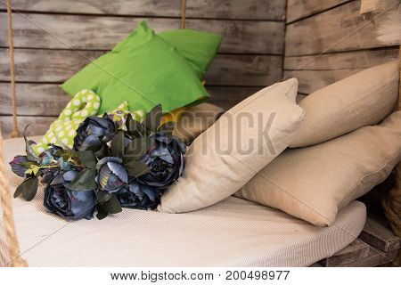 Suspended Seat With Cushions And A Bouquet Of Flowers