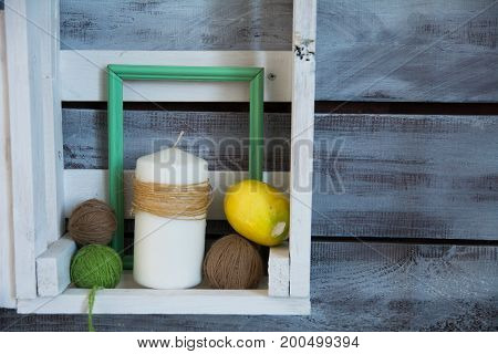 Wooden Shelf With Tangles Of Yarn And A Candle