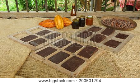 Handmade chocolate blocks inside wooden molds, ripe cocoa fruits and glass jars with cocoa products on a jute covered table