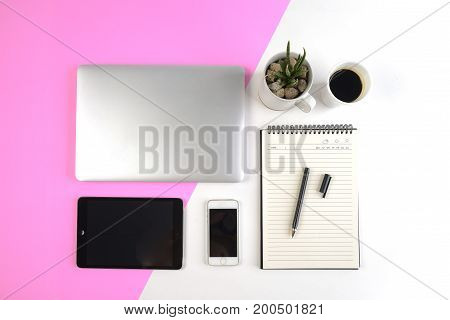 Office table with laptop computer notebook digital tablet and smartphone on modern two tone (white and pink) background.