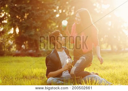 A loving couple of teenagers. Sudden picnic in the park at sunset. Teens drink soft drinks sitting on the lawn. They communicate.