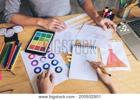 Two young dressmaker or designer colleagues working and discussing fashion project designers and drawing sketches for clothes profession and job occupation Fashion Designer Stylish Concept.
