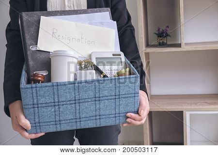 business woman carrying packing up all his personal belongings and files into a brown cardboard box to resignation in modern office resign concept.