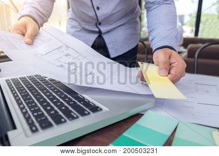 interior Creative creativity graphic designer working with graphics laptop blueprint and colour chart at workplace on wooden desk colour ideas style concept.