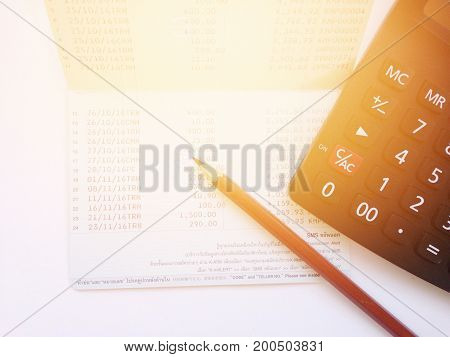 Business, finance, savings or mortgage background concept ; Pen, calculator and savings account passbook on white background