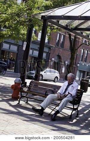 Burlington, Vermont - August 4, 2012 -- Vertical of an older gentleman taking a rest on a bench at the