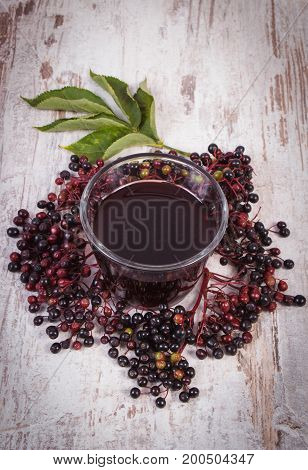 Bunch of fresh elderberry with green leaves and glass of elderberry juice on old rustic board healthy nutrition alternative medicine and therapy