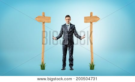 A businessman standing between two wooden signs pointing to different directions. Business strategy. Crossroads. Hard financial decisions.