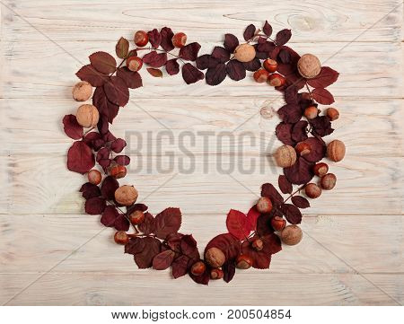 Flat lay frame in the form of a heart of autumn crimson leaves hazelnuts and walnuts on a light wooden background. Selective focus.