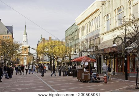 Burlington, Vermont - November 11, 2013 - Wide view of street vendors stores and crowds of people on the main street of the