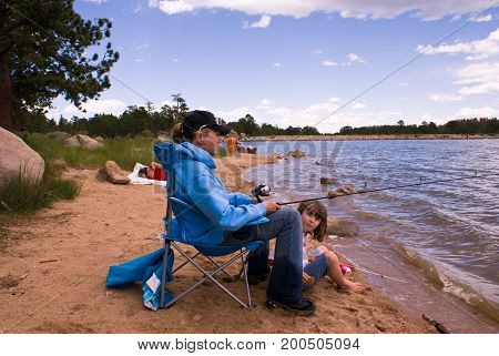 Grandmother fishes with her granddaughter while the daughter naps.