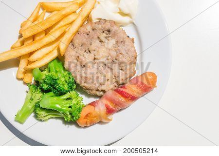 Minced Pork Steak Sausage and bacon roll with French Fries and broccoli on the plate isolated close up on white background from top-view
