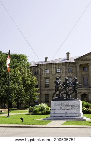 Charlottetown, Prince Edward Island - August 21, 2011 - Vertical of a statue of three soldiers in front of a government building with Canadian flag flying on a pole to the left near Charlottetown, Prince Edward Island on a bright sunny day in August.