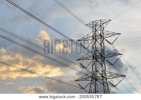 Silhouette of electricity post in evening day. High voltage power line.