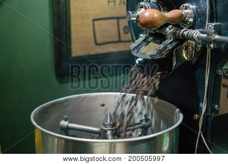 Arabica coffee beans in coffee machine roasting process.Coffee roasters machine. roasted coffee beans in spinning cooler professional machine