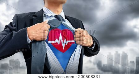businessman in superhero costume with heartbeat with city background